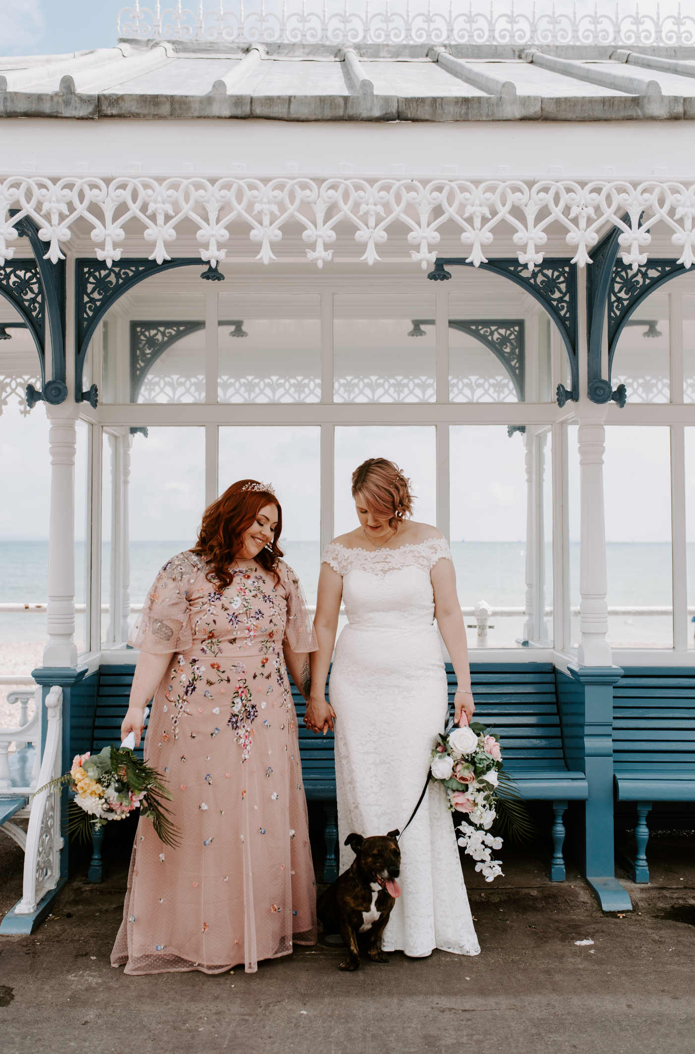 Emma and Abi in their wedding dresses holding hands with Tia the staffie in the middle. They are in a victorian shelter on weymouth seafront.