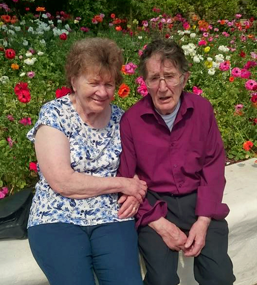 Shirley looking well, with her husband John sitting in front of some flowers