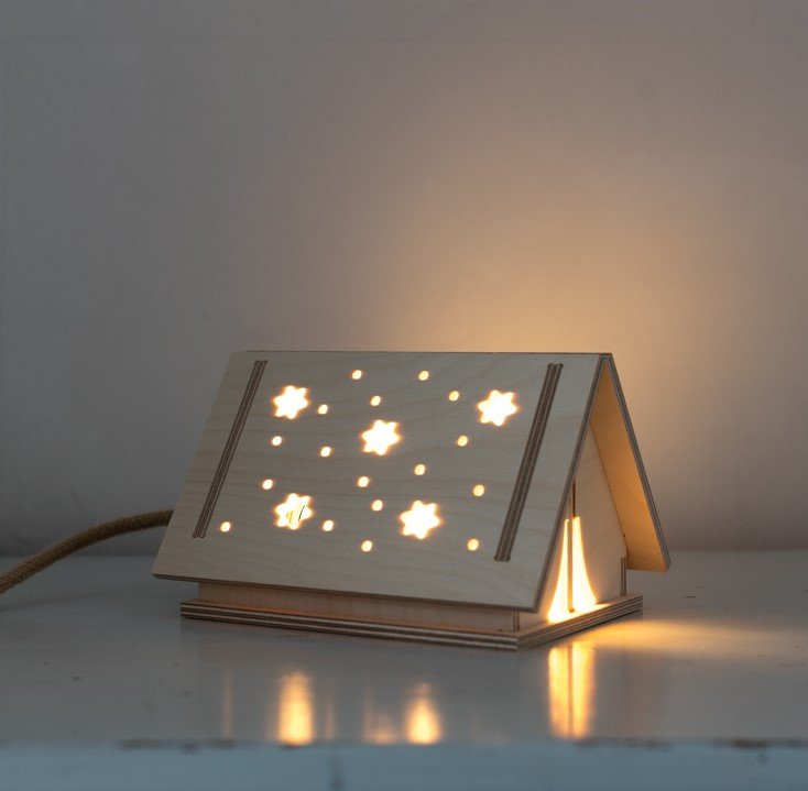 nightlight in the shape of a tent in wooden skandi style with star shape holes for the light to come throuhh