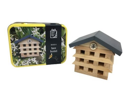 image of a wooden bug house which looks like a real house, next to the tin it comes in