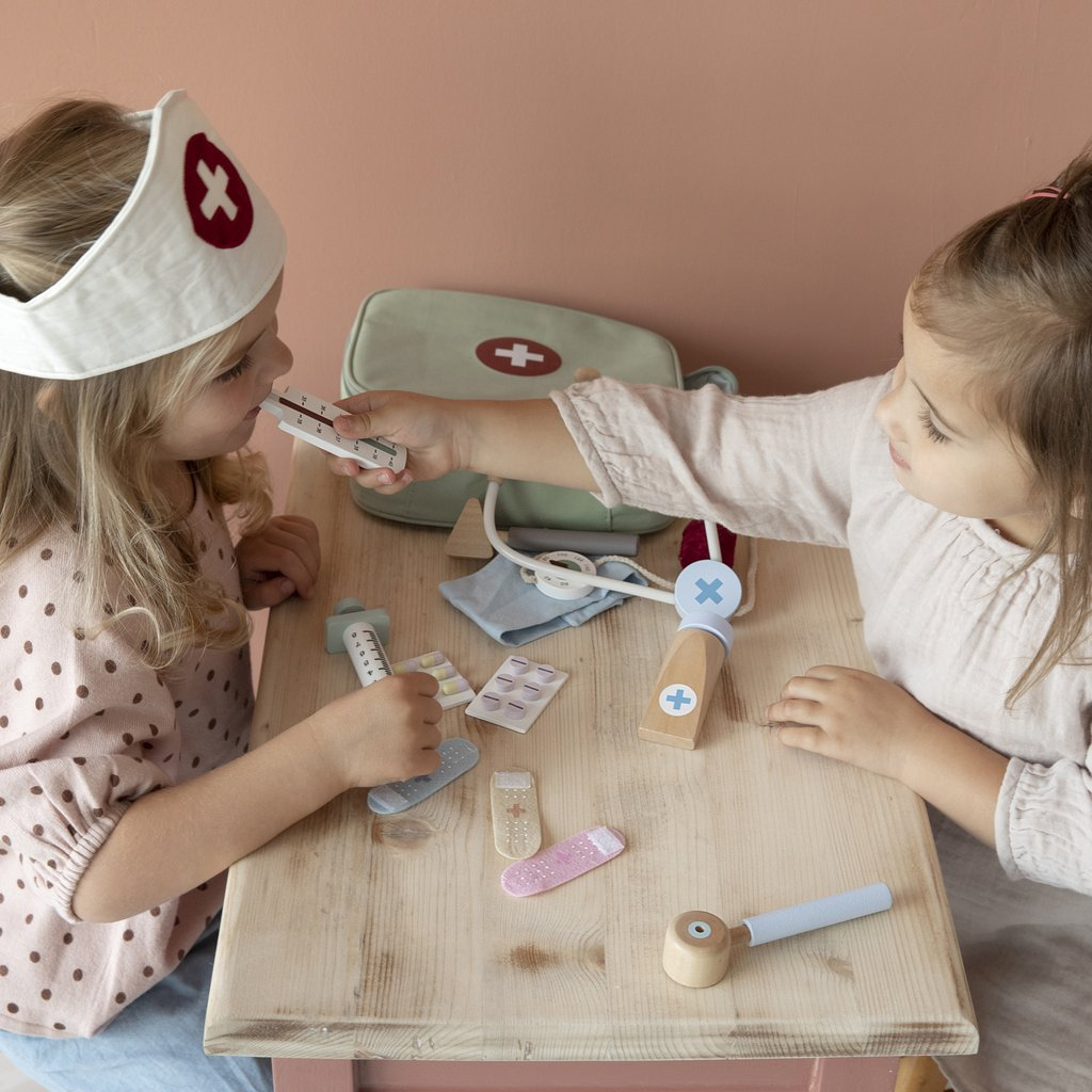 two children playing with a doctors set which is wooden with hints of pastel blue