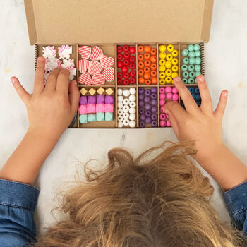 a flatlay image of a card box of wooden colourful beads with a toddlers hands reaching in