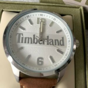 tan leather strap embossed with timberland logo, white face with silver edges, numbers for 12 and 6 and dashes around for other numbers, timberland written in silver across the white face. sits on cushion in branded box.