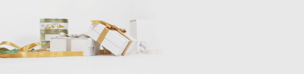 white boxes and candles against a white background with gold ribbon