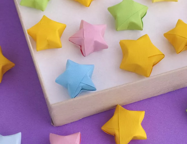 a selection of mini origami stars made with different coloured card