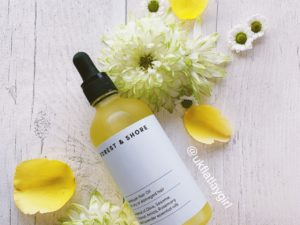 a bottle of hair oil sitting on yellow flowers