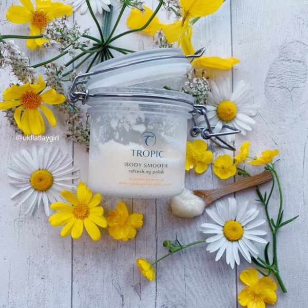 a flatlay of a jar of tropic scrub on a background of yellow flowers