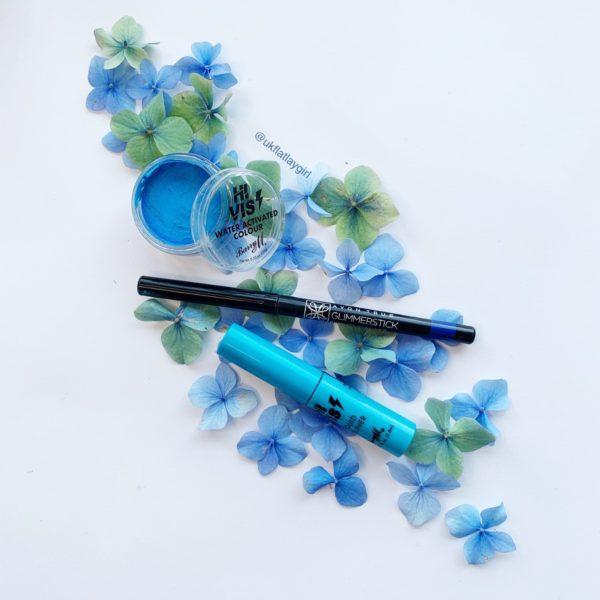beauty products sitting on blue hydrengea flowers
