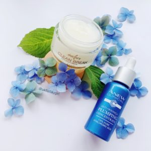 skincare products sitting on some blue hydrengea flowers