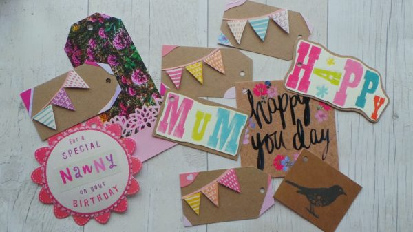 Selection of gift tags in bright colours backed onto Kraft card