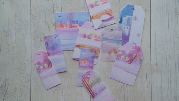 Pastel coloured gift tags featuring snowy watercolour style scenes