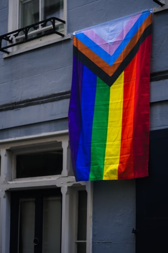 An image of the Pride Progress Flag hanging from a building