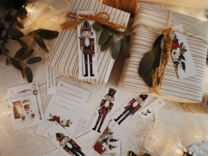 Long tags showing nutcrackers as well as large white tags with wording and Garland detail, shot from above with wrapped presents.