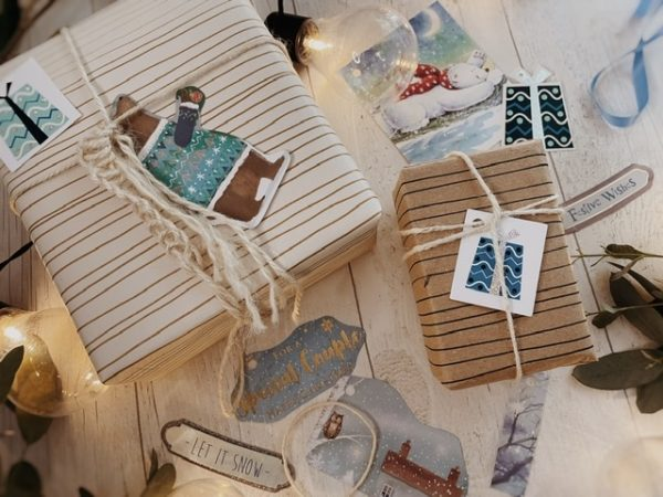 Pale blue tags some in wobbly shapes, some square, featuring polar bears and wrapped gifts. Styled on boxed tied with string.