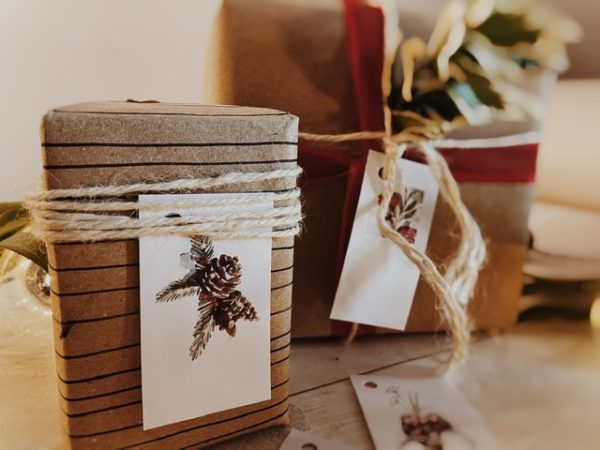 Image of a couple of the tags used on presents. Tags mainly white, one with a pine cone at the bottom and some fir, the other with winter berries and fir at the top. Other tags are pieces of a Garland with hanging baubles.