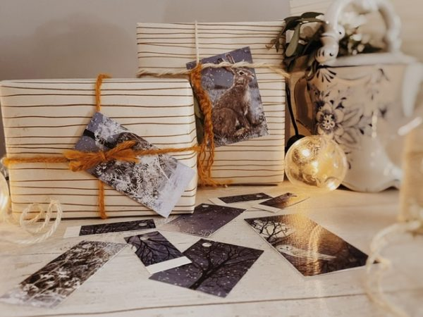 Square and rectangle greyish indigo tags featuring branch sillouhettes, one with an owl and moon and another with a rabbit or hare in snowy grass. Laid on a table with bulb shape string lights and presents tied with string.