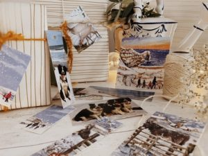 Selection of painted or photography style dorset scenes and dogs styled against wrapped gifts tied with string