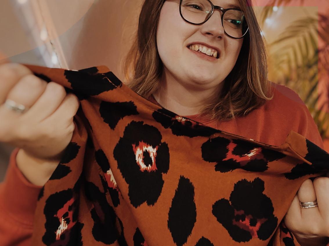 BUTTON - The Store. Image of Emma folding an orange dress.