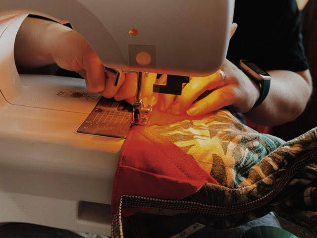 Hands working on a sewing machine running through a gift bag.