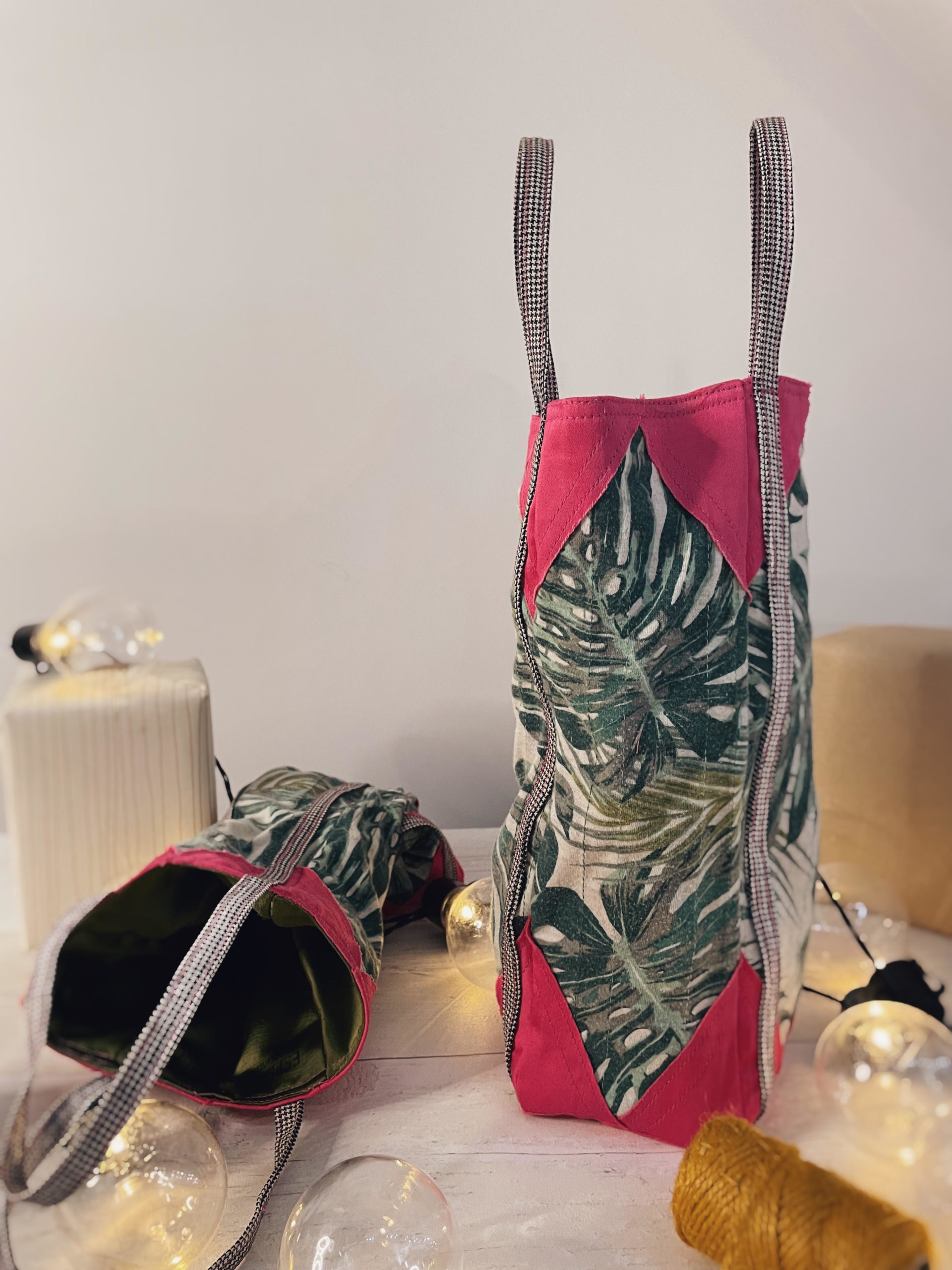 Emma bottle bag with green leaf fabric and pink corners,sat on a table with some wrapped gifts.