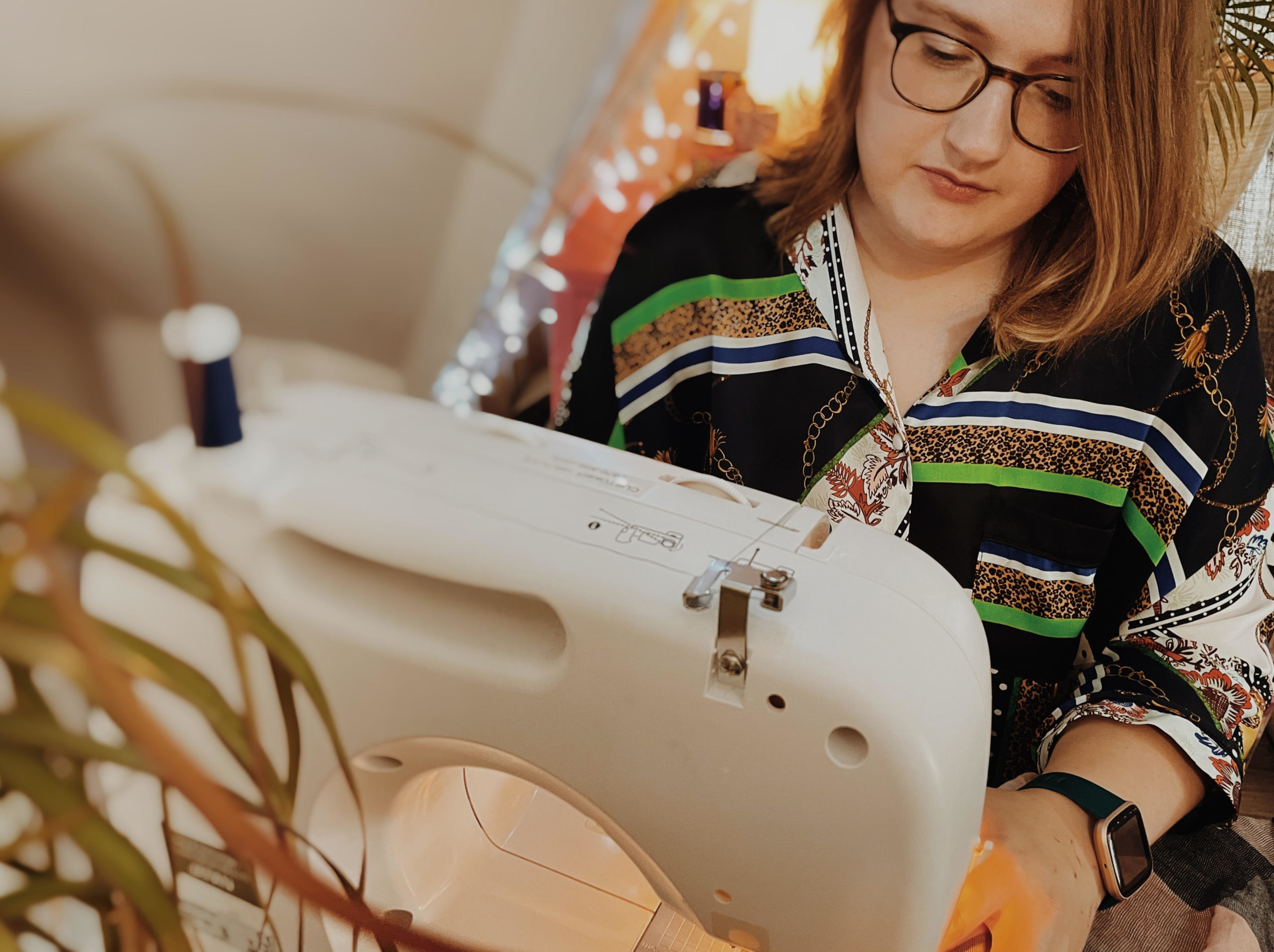 An image of Emma sitting at her sewing machine. Fairy lights add peaceful mood in the background.