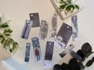 Soft cobalt and teal blue tags featuring snowy scenes including a couple who could be mixed gender or female facing away looking at the moon.
