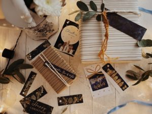Dark blue tags with gold details including some nativity scenes and pine cones and wreaths styled with rope and eucalyptus onto parcels.
