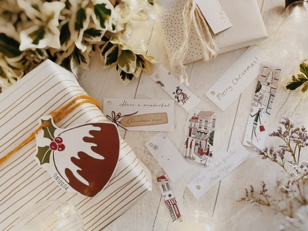 Mostly white tags featuring festive messages, shop illustrations and one with a big Christmas pud.