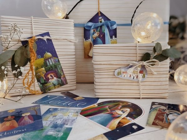 Selection of mostly blue jewelled tone tags with nativity and Christian Christmas illustrations in a watercolour type design. Also one more childlike cartoon illustration of 3 wise men. Styled on some boxes with string and eucalyptus.