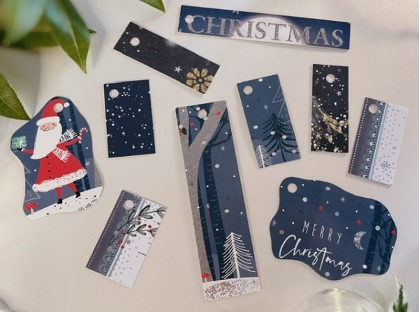 Dark teal tags with silver and white trees, mostly rectangular with a couple of wiggly shapes, one featuring a cute Santa!