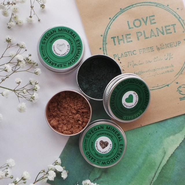 mineral eyeshaddow pots in aluminium tins sit against a white background with a green watercolour sheet over one half of the image. In the top corner is a paper sample of make up and there are babys breath flowers around the edges.