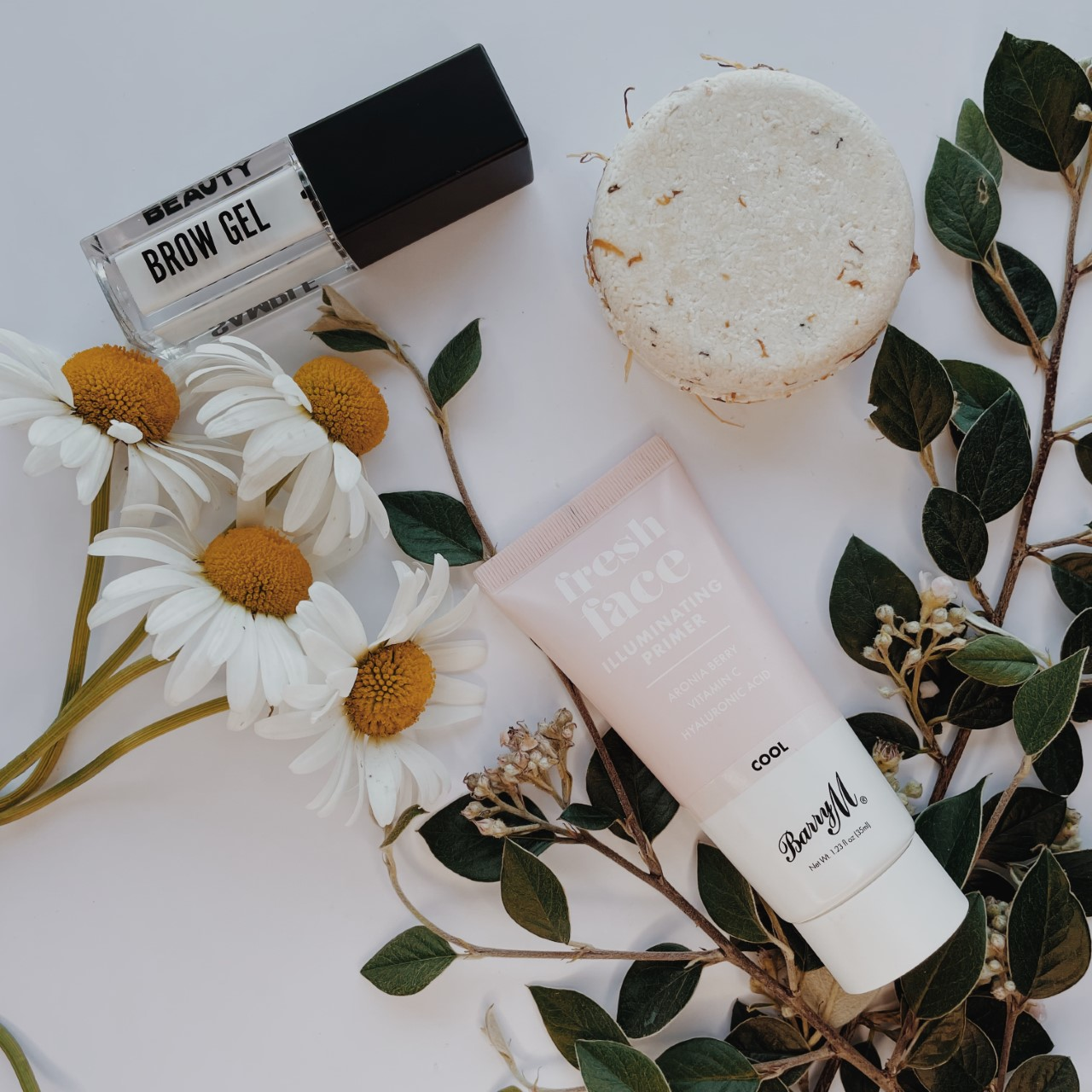 three beauty products: shampoo bar, face primer and eyebrow mascara in neutral colours all sit against a white background. A bunch of daisies peaks across from the left, and some leafy branches on the right.